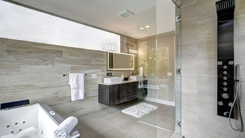 Contemporary master bathroom features a dark vanity cabinet fitted with rectangular his and hers sink, jetted tub and walk-in shower. Northwest, USA