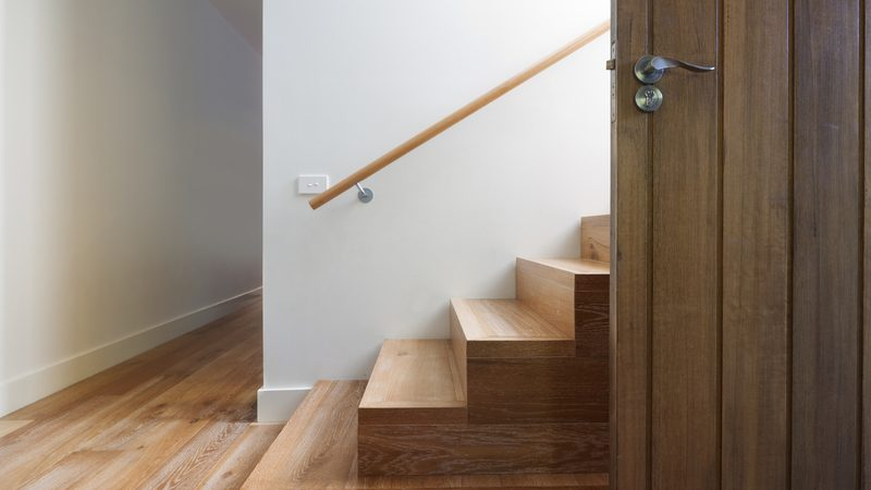 corner wooden staircase on wooden floors and white wall