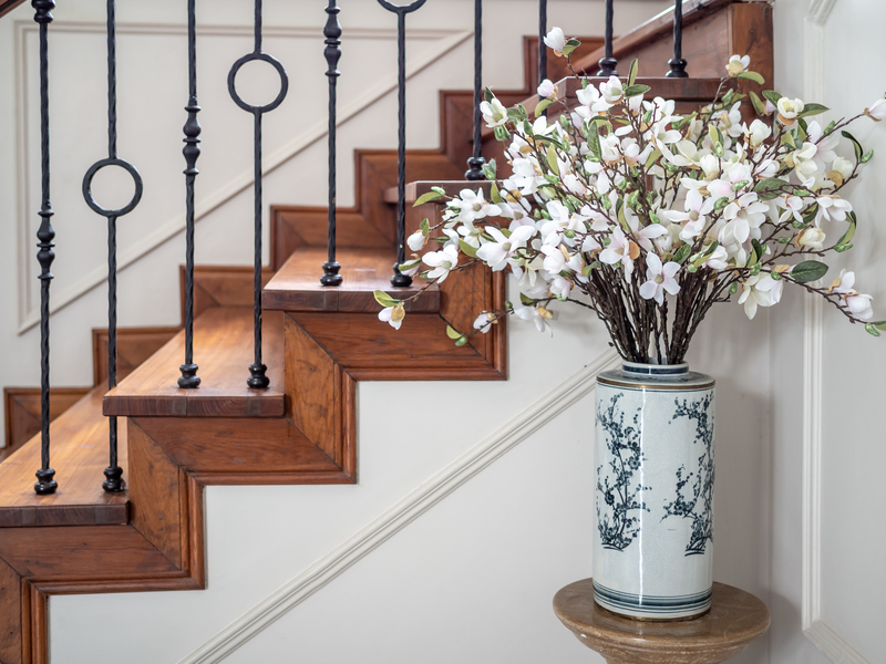 classic vintage elegant wooden staircase with wrought iron railing.
