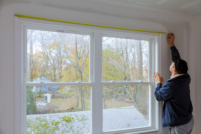 man measuring window ready for the build of the new timber windows