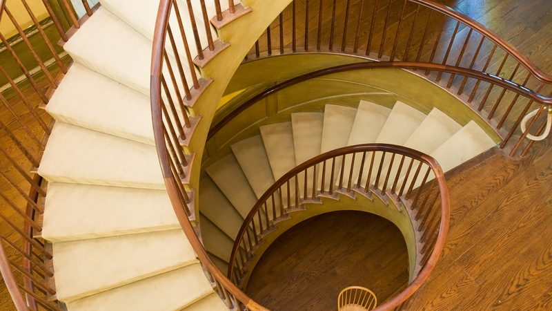 Spiral staircase with cream carpet and woonden handrail